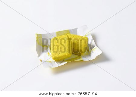 two cubes of herb instant broth in a paper