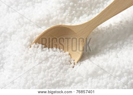 wooden spoon immersed in the portion of pure sea salt