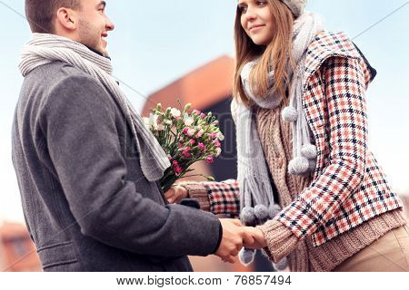 A picture of a romantic couple with flowers meeting in the city