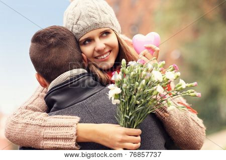 A picture of a happy woman with Valentines gift and flowers hugging her man