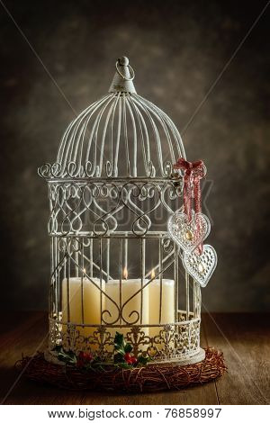 Glass heart shaped decorations on birdcage filled with candles
