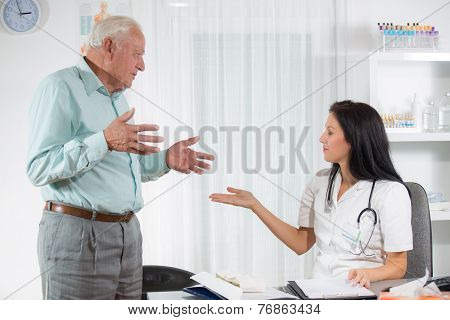 Doctor talking to her male senior patient at office, selective focus