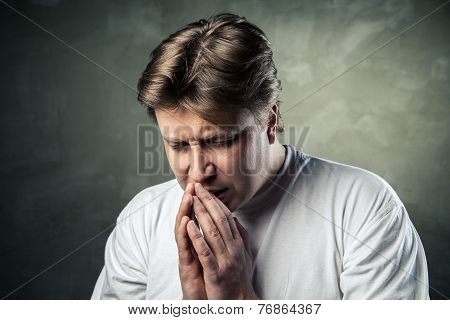Young man praying on dark background