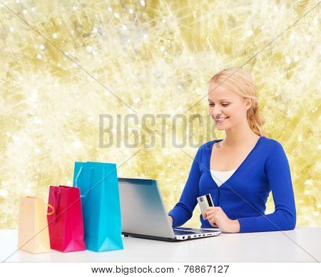 christmas, holidays, technology and shopping concept - smiling woman with shopping bags, credit card and laptop computer over yellow lights background