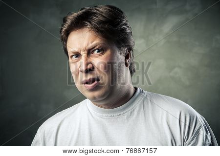 Man with disgusted expression over dark grey