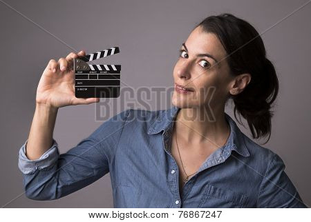 Smiling attractive woman in jeans shirt holding a movie clapper