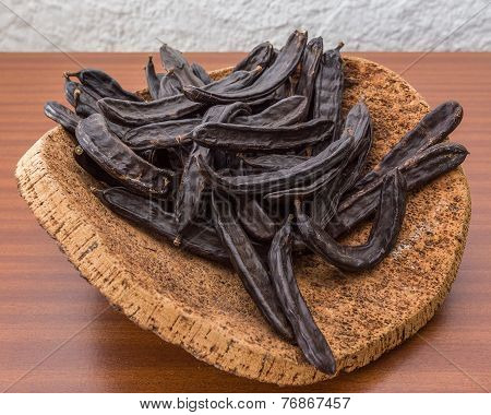 Carob Pods On Cortical Stand. On The Table.