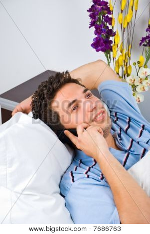 Man Lying On Bed Talking By Phone