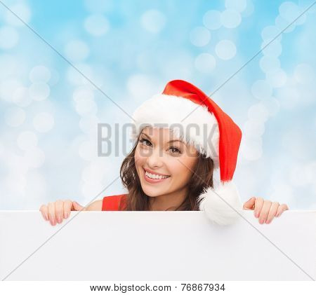 christmas, x-mas, people, advertisement and sale concept - happy woman in santa helper hat with blank white board over blue lights background