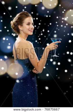 party, drinks, holidays, christmas and people concept - smiling woman in evening dress holding cocktail over night lights and snow background