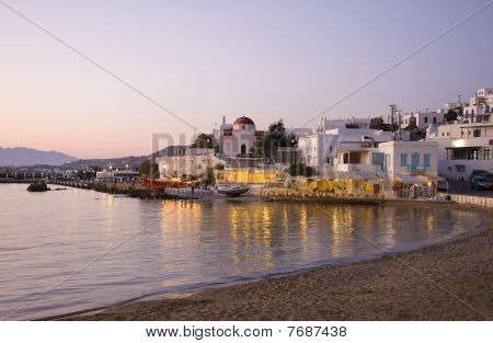 Sunset On Mykonos Island - A Building, A Church And A Restaurant Near The Sea