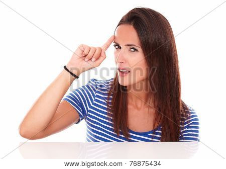 Reflective Young Woman Pointing To Her Forehead