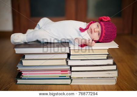 baby sleeping on stack of books