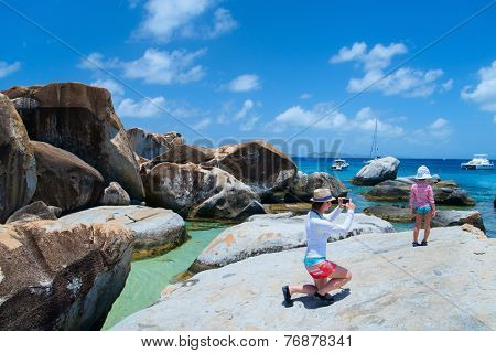 Mother photographing her little daughter at The Baths beach area major tourist attraction at Virgin Gorda, British Virgin Islands, Caribbean