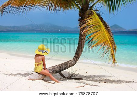 Back view of adorable little girl at tropical beach sitting on palm tree during summer vacation
