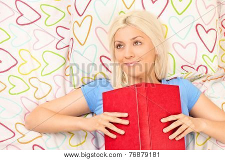 Joyful girl reading a book on a bed with colorful sheets