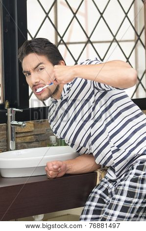 young man brushing his teeth