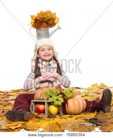 girl with fruits and vegetables on autumn leaves on white