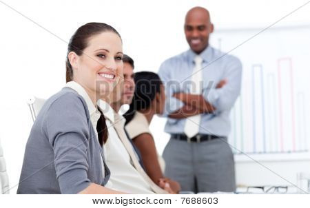 Smiling Businesswoman Looking At The Camera During A Meeting With Her Team