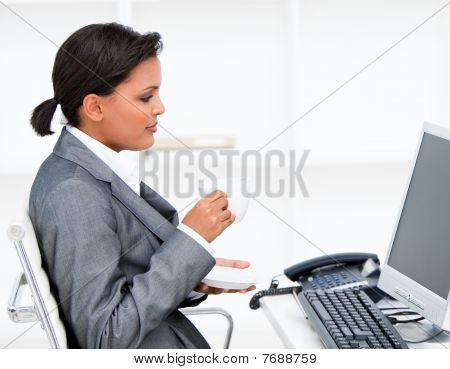 Attractive Businesswoman Drinking A Coffe While Working At A Computer
