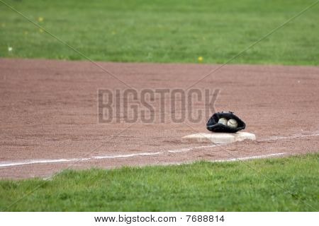 Baseballs In Glove On Playing Field