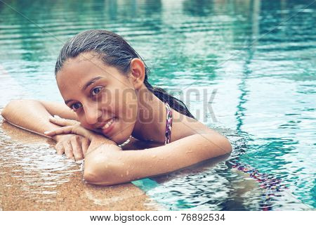 Contemplative young Asian woman in a sparkling blue swimming pool resting her head on her arms on the pool surround looking to the side with a pensive serious expression, close up of her face