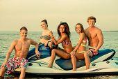 image of ski boat  - Group of happy multi ethnic friends sitting on a jet ski - JPG