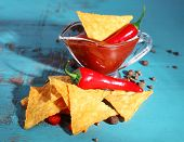 picture of nachos  - Tasty nachos and bowl with sauce on color wooden background - JPG
