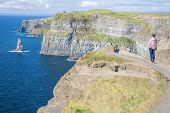 foto of cliffs moher  - Young woman at The Cliff of Moher Co - JPG