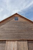 picture of dairy barn  - Wooden barn roof with blue sky background - JPG