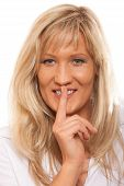 stock photo of hush  - Woman asking for silence or secrecy with finger on lips hush hand gesture - JPG