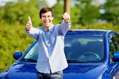 stock photo of stand up  - Young happy man in glasses standing in front of his new car and showing thumb up and car key - JPG