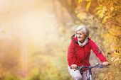 foto of bike path  - Active senior woman ridding bike in autumn nature. ** Note: Shallow depth of field - JPG