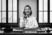 picture of receptionist  - Smiling vintage receptionist working at office desk and smiling  - JPG