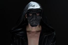 foto of madman  - Photo of the madman in handmade mask on black background - JPG