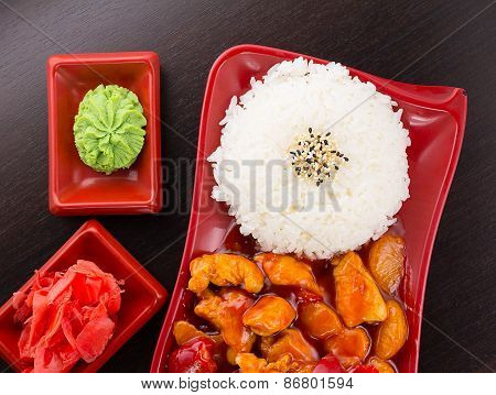 Sweet And Sour Chicken With Rice On A Plate