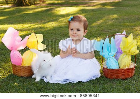 Happy Smiling  Baby Girl With White Rabbit And  Easter Chocolate Eggs