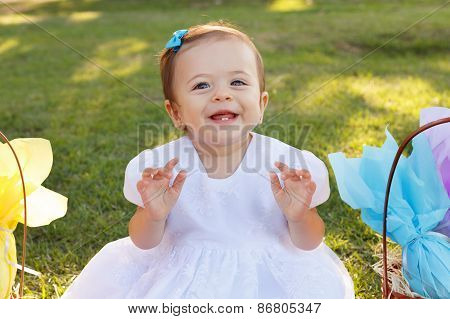 Cute Little Baby Girl In White Dress Near Wicker Basket With Gifts In Park On Green Grass