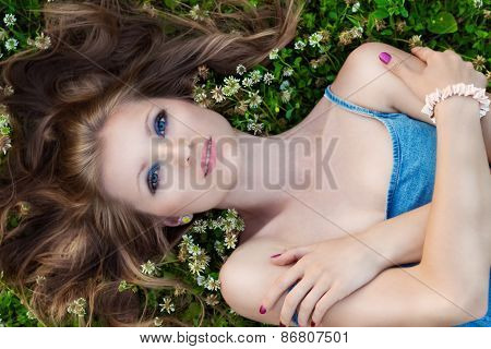 beautiful sexy girl with bright makeup is lying on the grass and flowers on a Sunny summer day