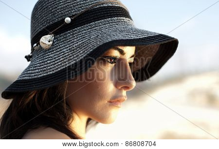 Photo of a beautiful woman in black stylish hat, closeup portrait of gorgeous young lady with natural makeup, side view of lovely charming Arabic female outdoor