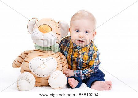 Studio portrait of a little boy with a plush toy.