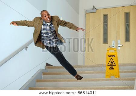 African American businessman falling on stairwell with yellow warning sign on steps