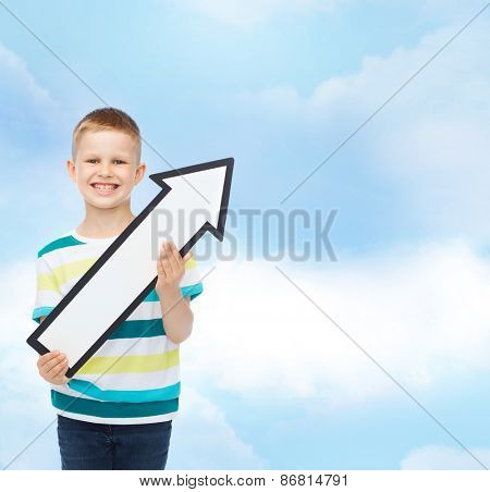 advertising, direction and childhood concept - smiling little boy with white blank arrow pointing up over cloudy sky background