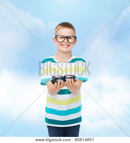 vision, health and people concept - smiling little boy in eyeglasses holding spectacles over blue sky with white clouds background