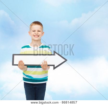 advertising, direction and childhood concept - smiling little boy with white blank arrow pointing right over cloudy sky background