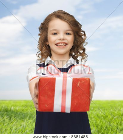 people, holidays, charity and children concept - happy girl with red gift box over blue sky and grass background