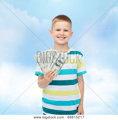 financial, planning, childhood and educational concept - smiling boy holding dollar cash money in his hand over cloudy sky background