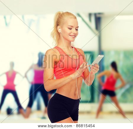 sport, fitness, technology, internet and healthcare concept - smiling sporty woman with smartphone and earphones