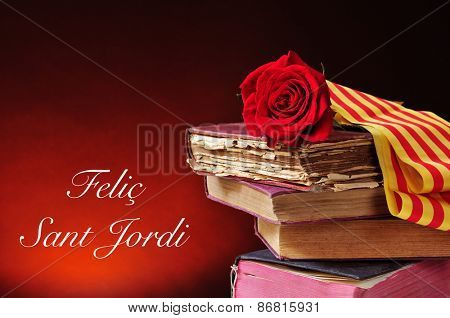 a red rose and the catalan flag on a pile of old books and the text Felic Sant Jordi, Happy Saint Georges Day, written in catalan, when it is tradition to give red roses and books in Catalonia, Spain