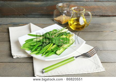 Green salad with cucumber and wild leek on wooden background